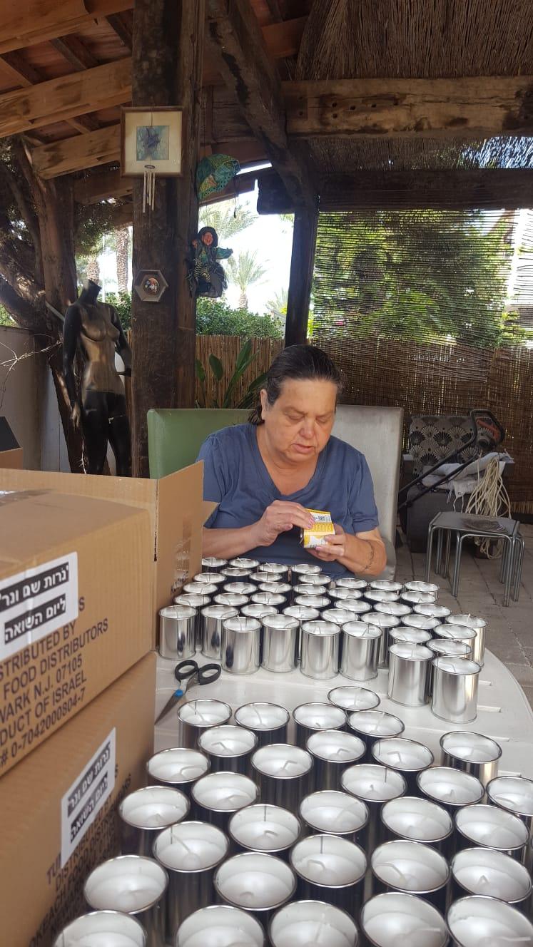 מתנדבת בהדבקת תוויות על נרות זיכרון אישיים