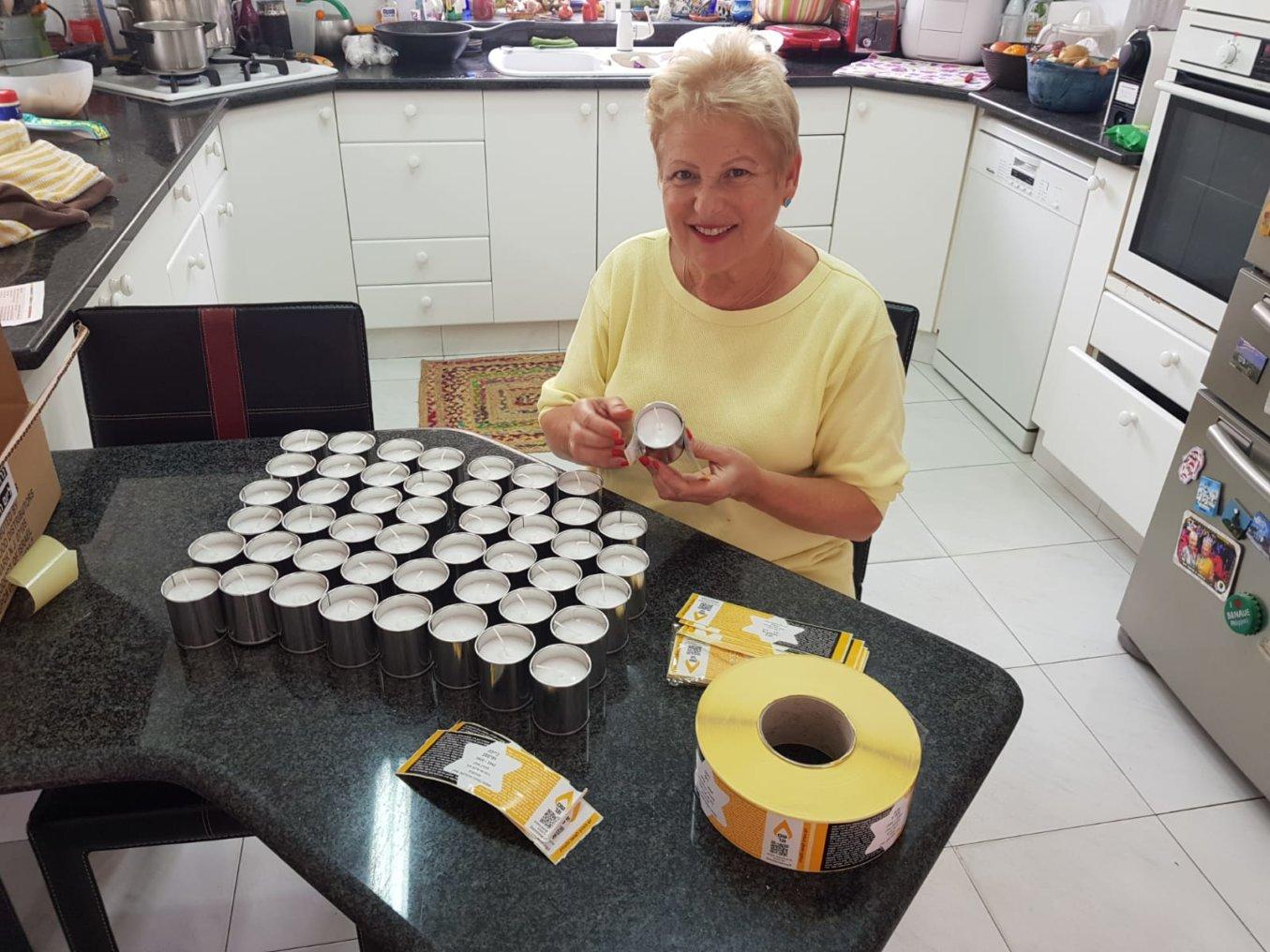 נורית אבנר מתנדבת בהדבקת תוויות על נרות זיכרון אישיים