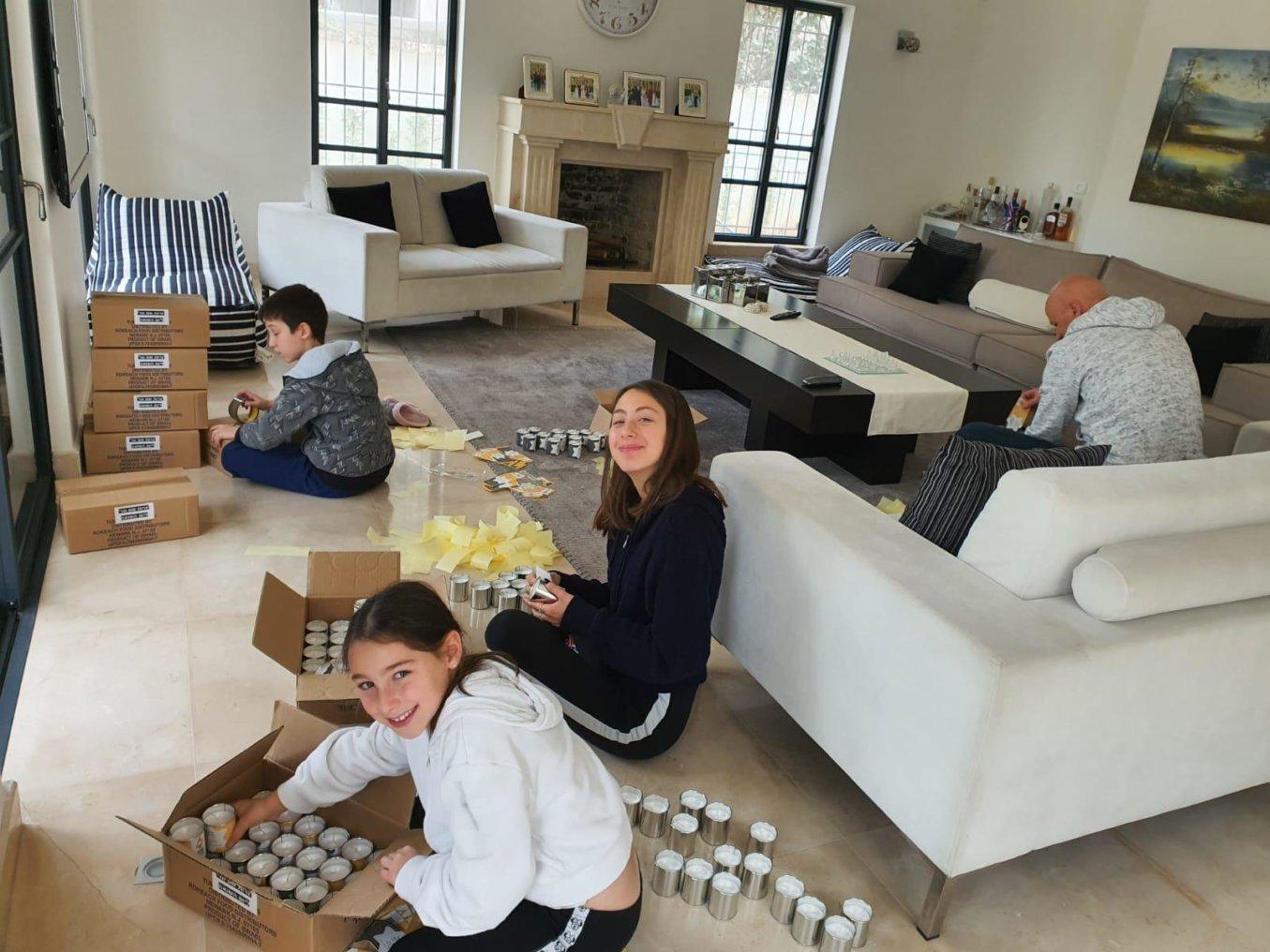 משפחת ליבני מתנדבת בהדבקת תוויות על נרות זיכרון אישיים