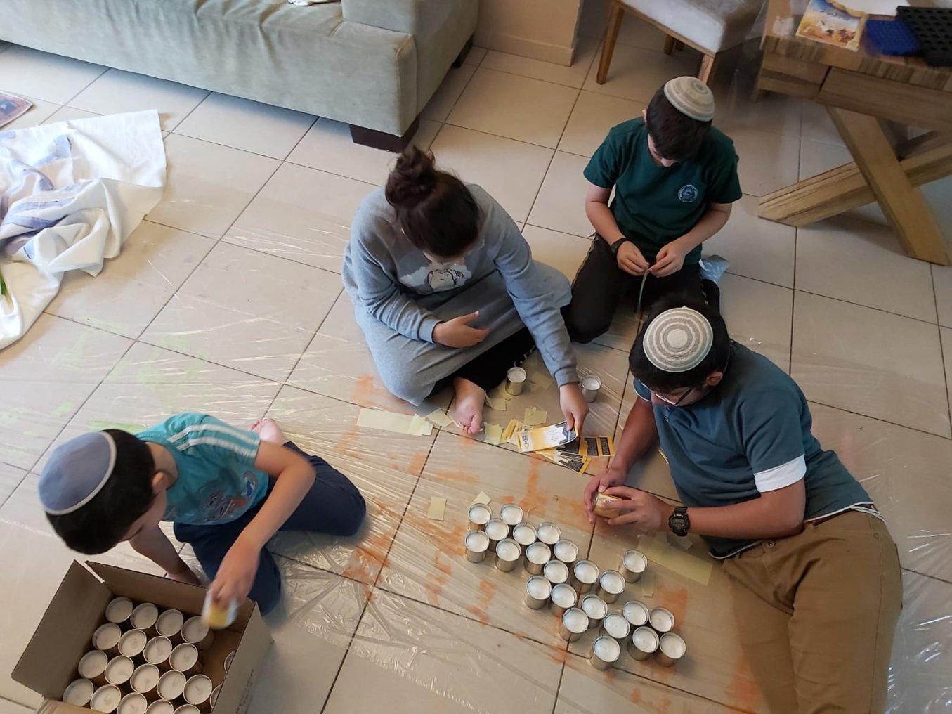 משפחת כהנא מתנדבת בהדבקת תוויות על נרות זיכרון אישיים